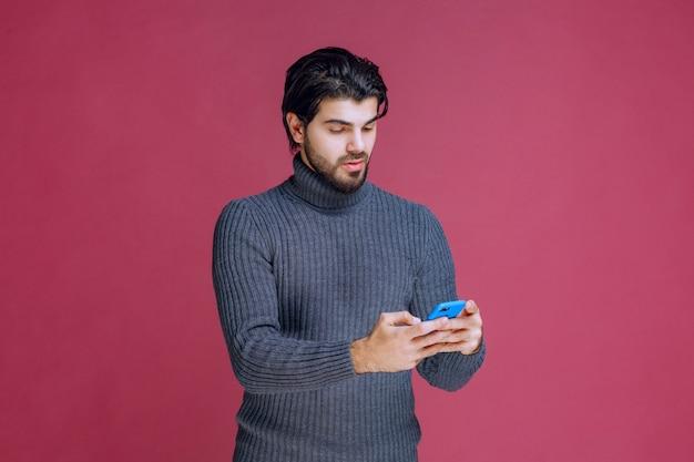 Homem segurando um smartphone, lendo mensagens ou mensagens de texto.