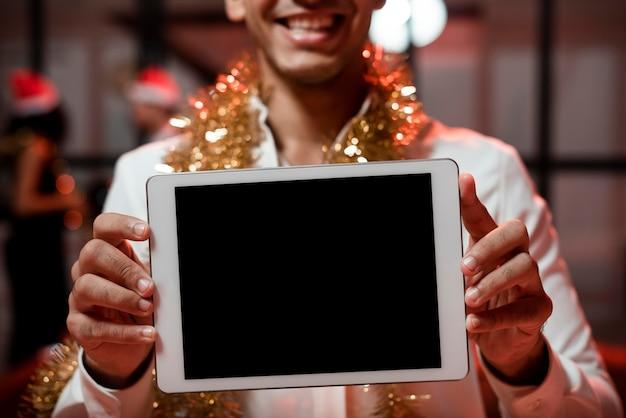 Homem segurando um tablet de tela vazia na festa de ano novo