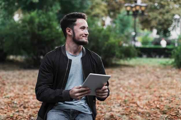 Homem segurando um tablet e desviar o olhar