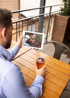 Homem segurando um tablet para videochamada enquanto bebe uma cerveja