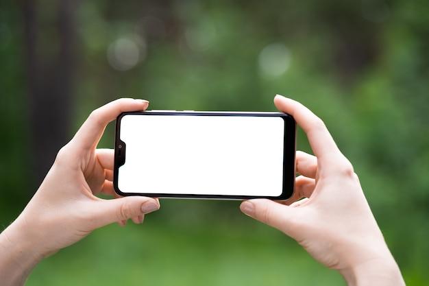 Homem segurando um telefone inteligente com fundo desfocado. para montagem de display gráfico.