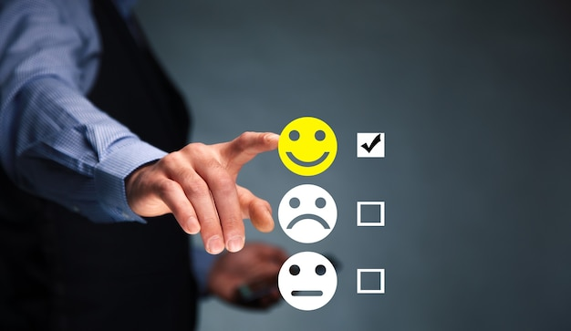 Homem segurando um telefone inteligente com um ícone de rosto sorridente