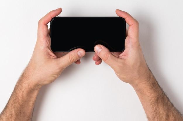 Homem segurando um telefone. tela preta vazia. fundo branco, cópia espaço