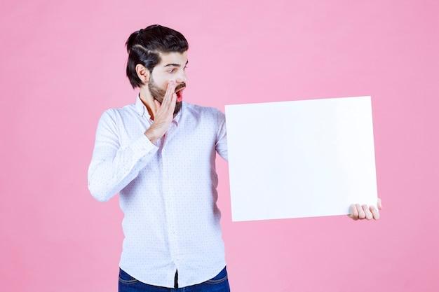Homem segurando um thinkboard quadrado branco e sussurrando.