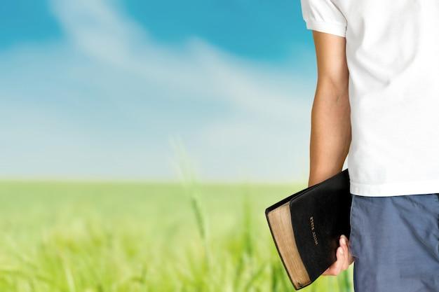 Homem segurando um velho livro da bíblia no fundo