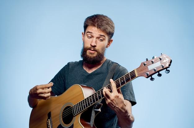 Homem segurando um violão cantando uma música com camiseta preta