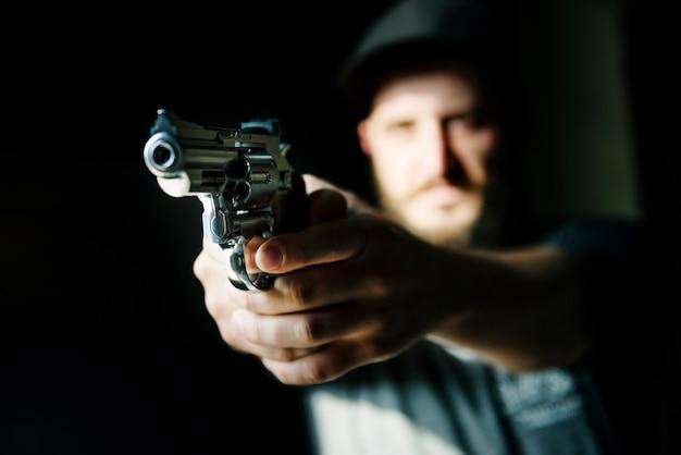 Homem, segurando uma arma com fundo preto