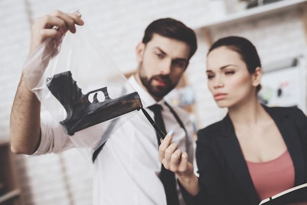 Homem segurando uma arma como prova enquanto a mulher está escrevendo.