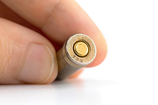Homem segurando uma bala de 9 mm em close-up com a parte inferior de cartuchos de bala em fundo branco isolado
