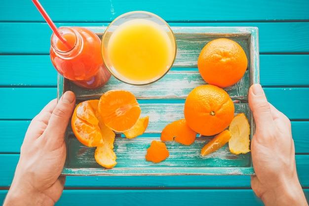 Homem segurando uma bandeja vintage com tangerinas e suco fresco nas mãos