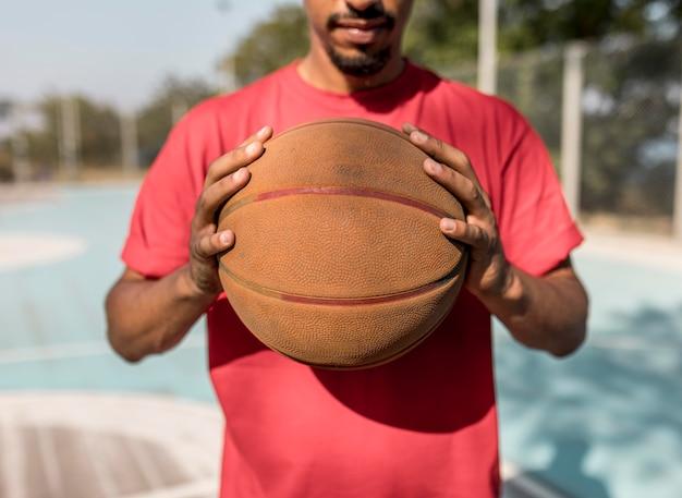 Homem segurando uma bola de basquete na frente dele