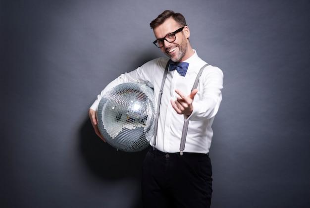 Homem segurando uma bola de discoteca