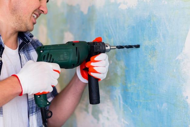 Homem segurando uma broca de martelo na parede