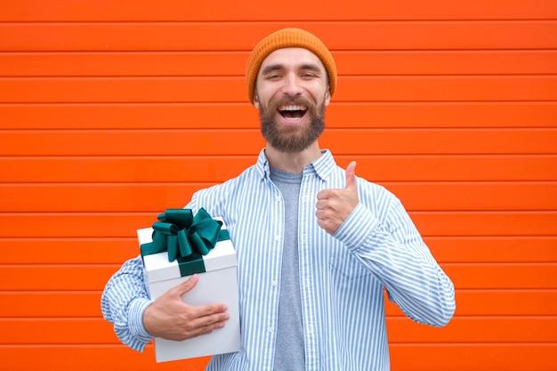 Homem segurando uma caixa branca com laço verde