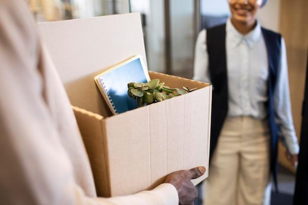 Homem segurando uma caixa de pertences e se acomodando em seu novo trabalho de escritório