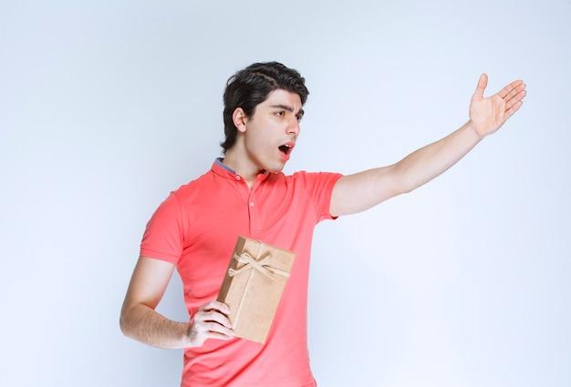 Homem segurando uma caixa de presente de papelão e apontando para algum lugar.
