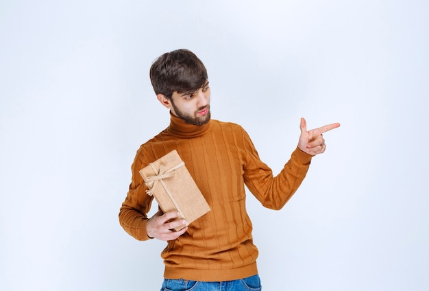 Homem segurando uma caixa de presente de papelão e chamando alguém do lado direito.