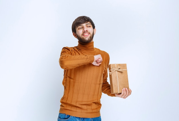 Homem segurando uma caixa de presente de papelão e mostrando sinal de prazer.