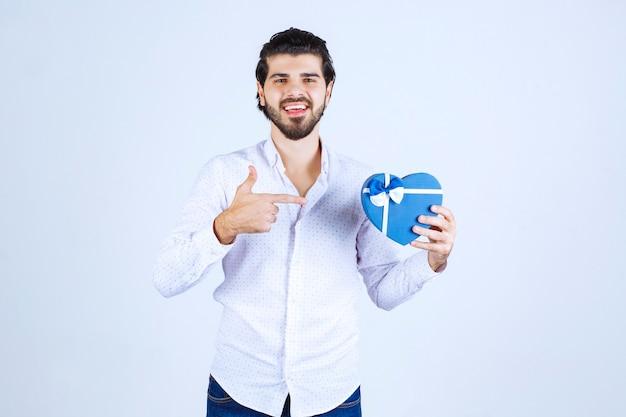 Homem segurando uma caixa de presente em formato de coração azul e mostrando o polegar