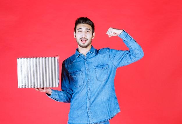 Homem segurando uma caixa de presente prata na parede vermelha e mostrando sinal positivo com a mão.