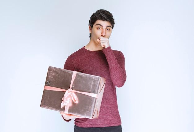 Homem segurando uma caixa de presente rosa e brincando.