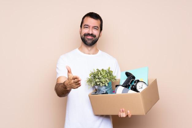 Homem segurando uma caixa e movendo-se em nova casa, apertando as mãos para fechar um bom negócio