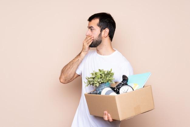 Homem segurando uma caixa e movendo-se em nova casa cobrindo a boca e olhando para o lado