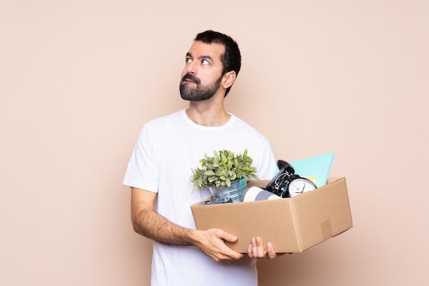 Homem segurando uma caixa e movendo-se em nova casa com confundir a expressão do rosto
