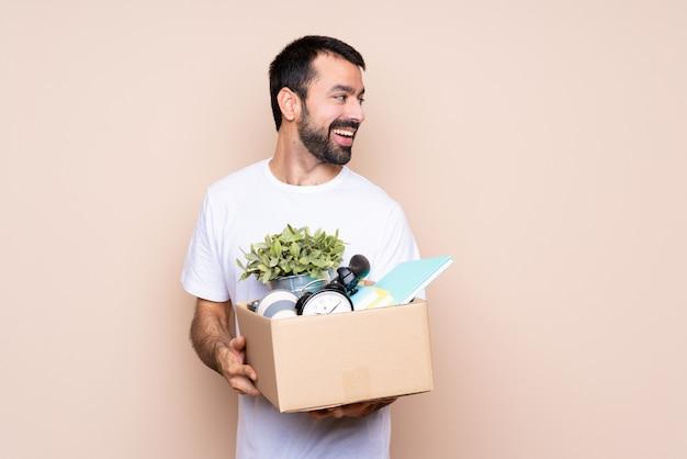 Homem segurando uma caixa e movendo-se em nova casa com os braços cruzados e feliz