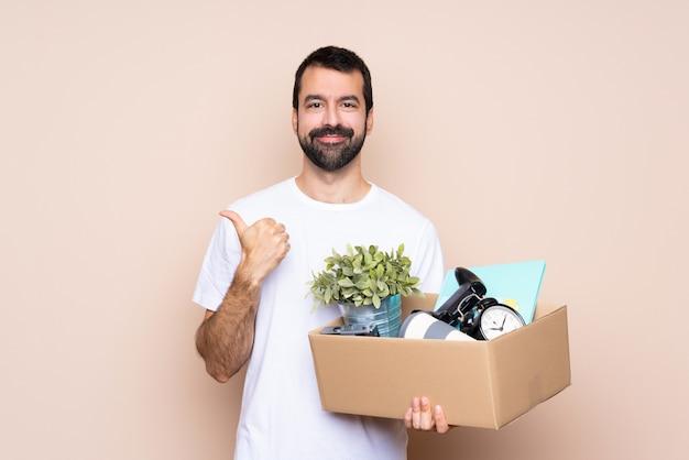 Homem segurando uma caixa e movendo-se em nova casa com polegares para cima gesto e sorrindo