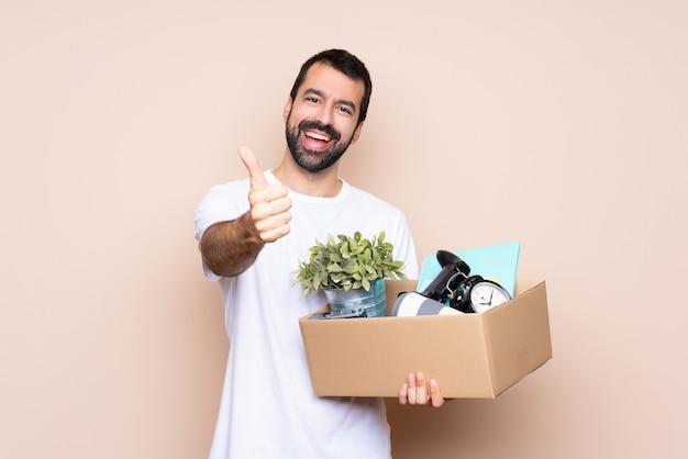 Homem segurando uma caixa e movendo-se em nova casa com polegares para cima porque algo bom aconteceu