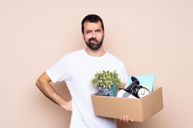 Homem segurando uma caixa e movendo-se em nova casa com raiva