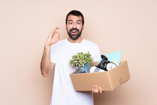 Homem segurando uma caixa e movendo-se em nova casa isolado surpresa e mostrando sinal okey