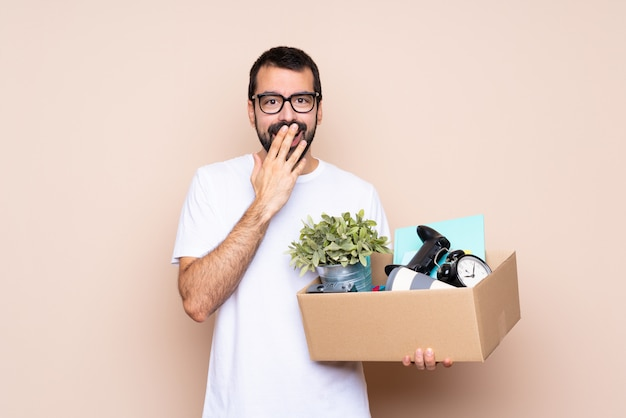 Homem segurando uma caixa e movendo-se em nova casa mais isolado com óculos e surpreso