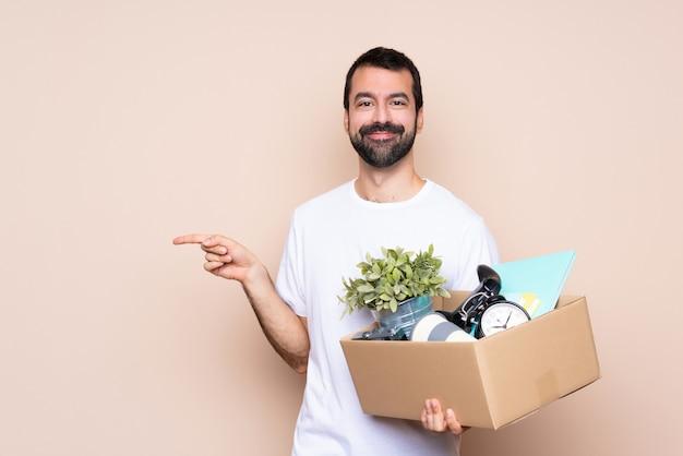 Homem segurando uma caixa e movendo-se em nova casa sobre dedo apontando isolado para o lado