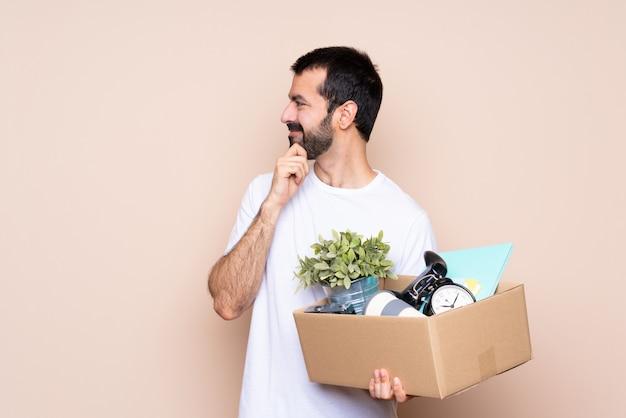 Homem segurando uma caixa e movendo-se em nova casa sobre fundo isolado, olhando para o lado