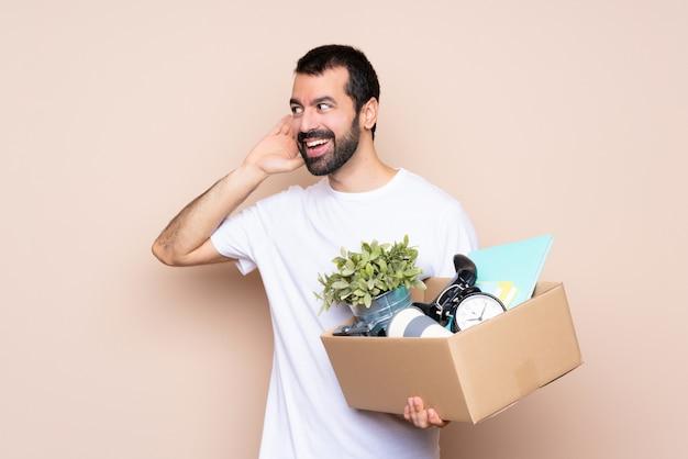 Homem segurando uma caixa e movendo-se em nova casa sobre fundo isolado, ouvindo algo, colocando a mão na orelha