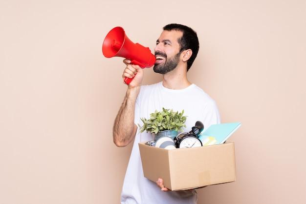 Homem segurando uma caixa e movendo-se em nova casa sobre isolado gritando através de um megafone