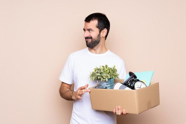 Homem segurando uma caixa e movendo-se em nova casa sobre isolado planejando algo