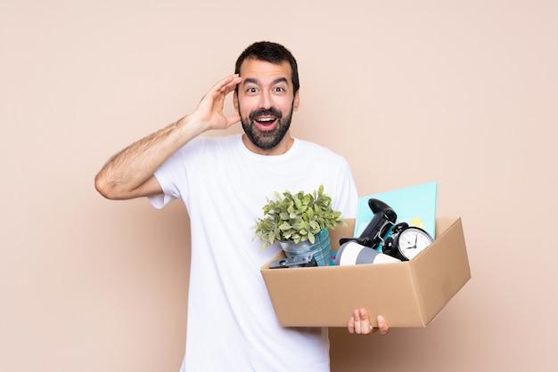 Homem segurando uma caixa e movendo-se em nova casa sobre parede isolada com expressão de surpresa