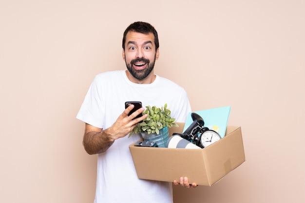 Homem segurando uma caixa e movendo-se em nova casa sobre parede isolada surpreendeu e enviando uma mensagem