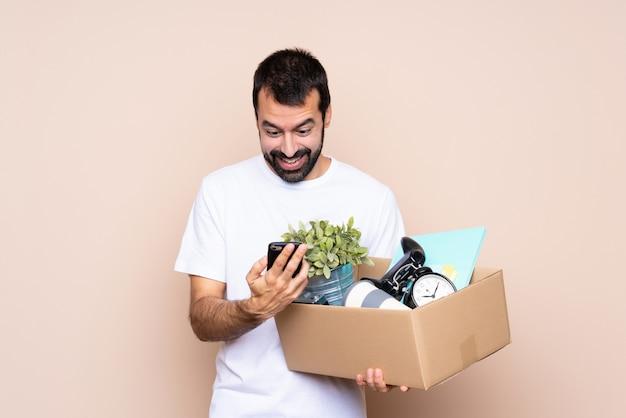 Homem segurando uma caixa e movendo-se em nova casa surpreso e enviando uma mensagem