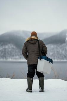 Homem segurando uma caixa para o peixe que pescou
