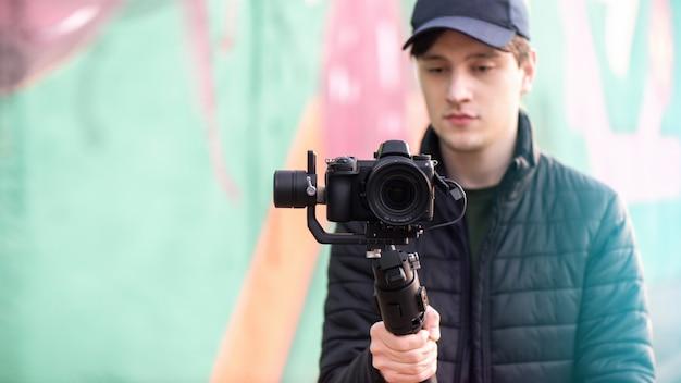 Homem segurando uma câmera na steadycam, fundo colorido