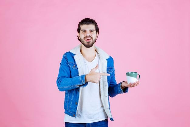 Homem segurando uma caneca de café e apontando para ela.