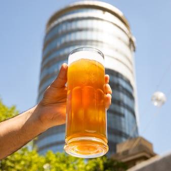 Homem segurando uma caneca de cerveja, vidro com plano de fundo do edifício
