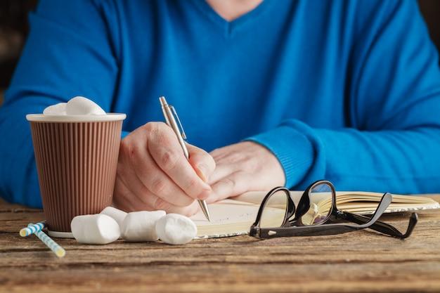 Homem segurando uma caneca de chocolate quente com marshmallows, inverno bebida de natal