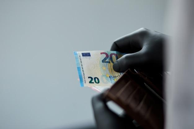 Homem segurando uma carteira com dinheiro euro na mão em luvas médicas pretas