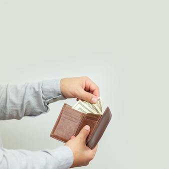 Homem segurando uma carteira de couro aberta cheia de dinheiro ou notas de dólar de papel