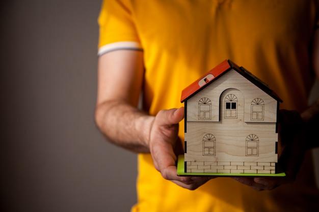 Homem segurando uma casa de madeira de brinquedo nas mãos